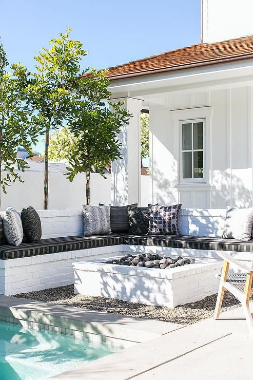 an L shaped white brick bench lined with black and white cushions facing a white brick fire pit and a ground pool