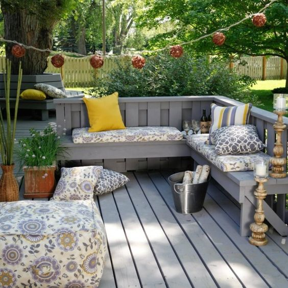 L-shaped grey wooden bench with cushions and pillows and a garland over it