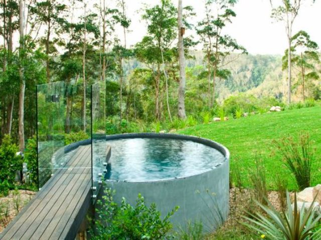 a free-standing jacuzzi with a wooden bridge and glass rails