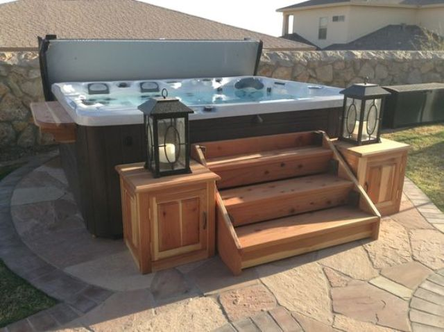 a jacuzzi with wooden stairs and lanterns on the corners