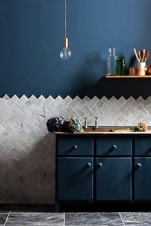 navy cabinets and a wall, marble tiles clad in a chevron pattern