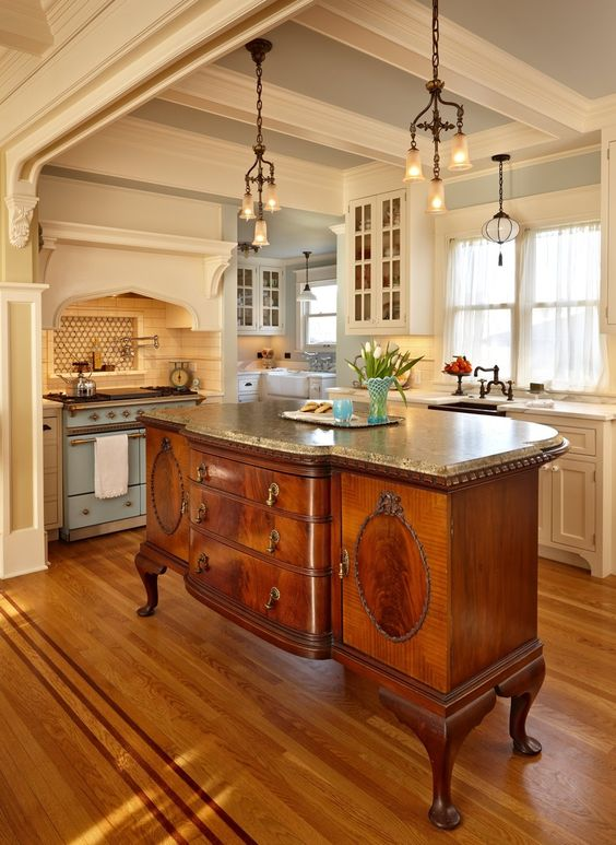 an antique French cabinet with a granite counter used as a kitchen island