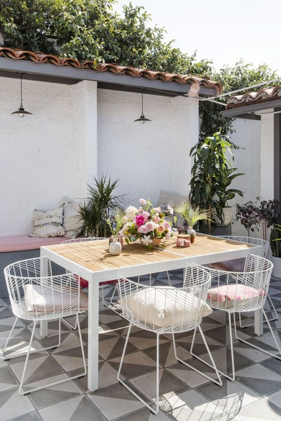 refined white metal chairs with pillows look chic and match the table on white  metal legs - 30 Awesome Outdoor Dining Area Furniture Ideas - DigsDigs