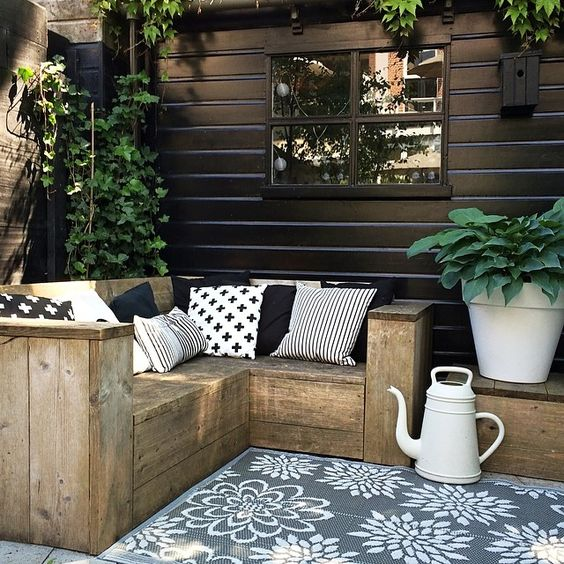 small rustic L-shaped wooden bench with graphic pillows for a Nordic terrace