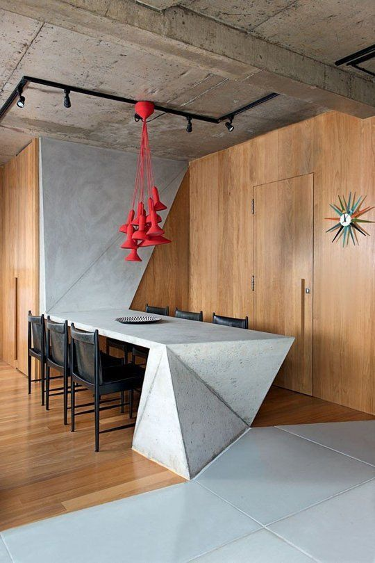 a concrete table with geometric design that goes up the wall and red pendant lamps