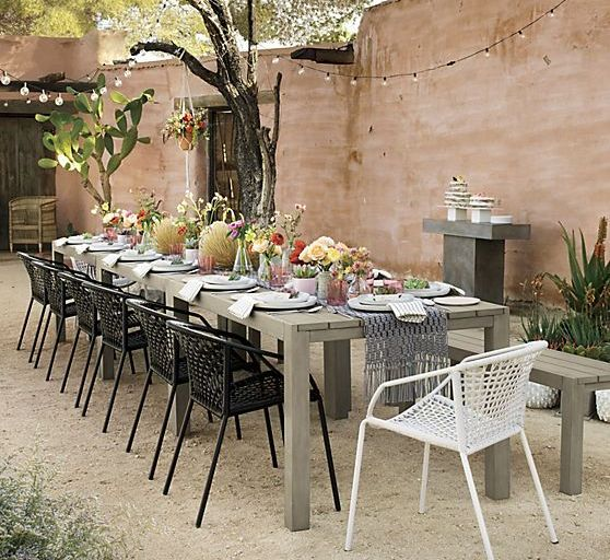 metal frame chairs with wicker contrast with a wooden table