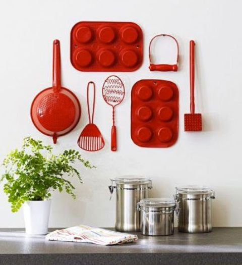 red reclaimed utensils on a kitchen wall will catch an eye and look super cute