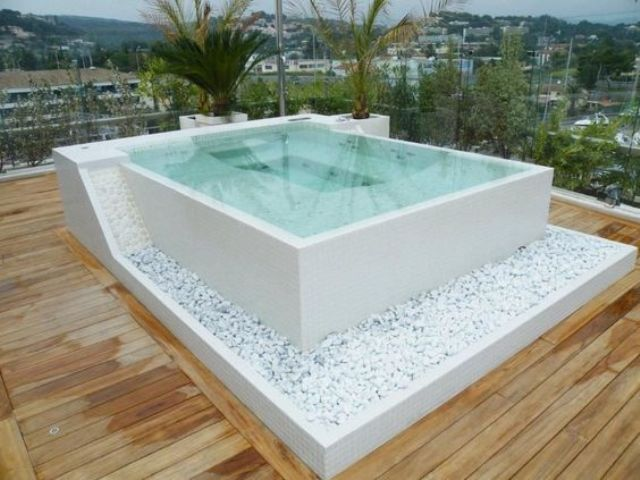 a square jacuzzi decorated with white pebbles on a wooden deck looks very natural and refined