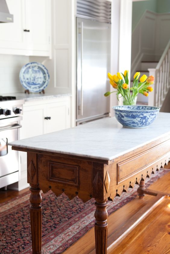 a vintage rustic table with carved legs and a marble counter