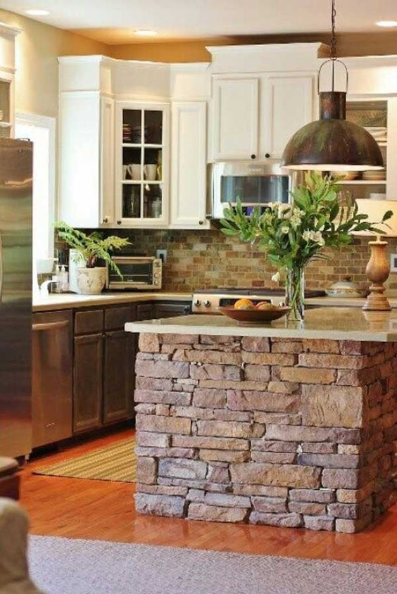 a brick clad kitchen island with a stone top looks textural