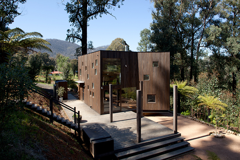 This vacation home clad with dark timber features a lot of piercings and glazings to bring the views inside and merge with nature
