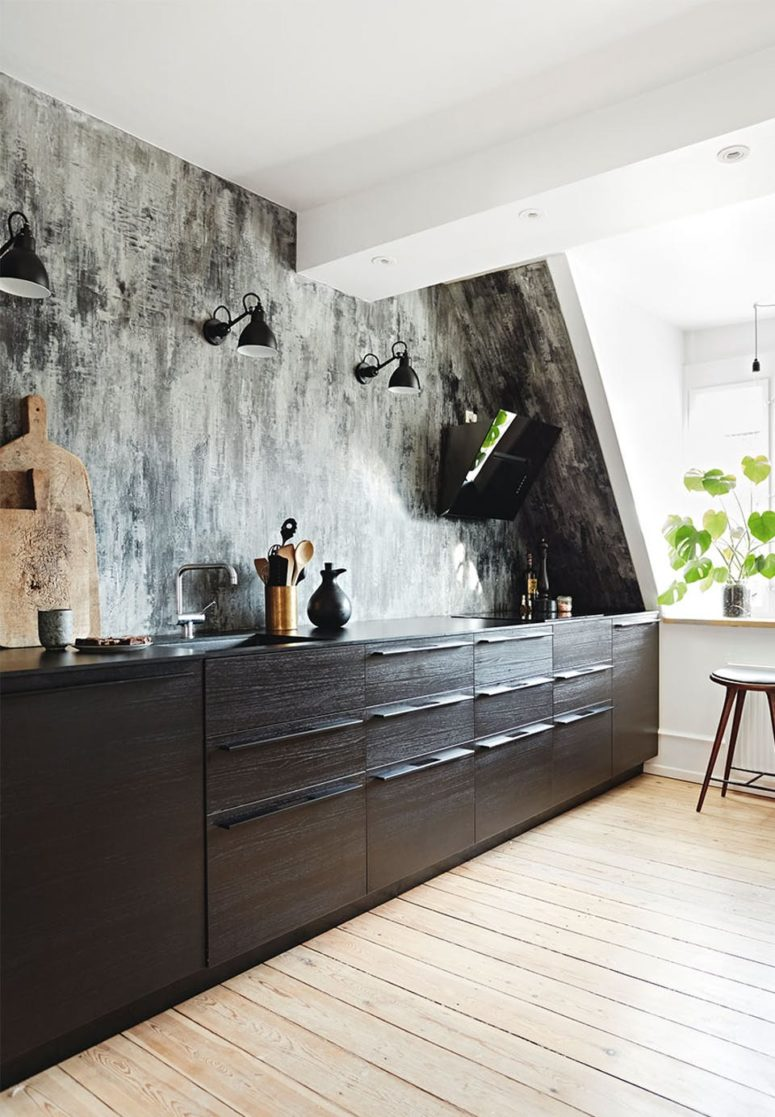 The kitchen features a graphic wallpaper wall as a backsplash, there are black cabinets and wall lamps