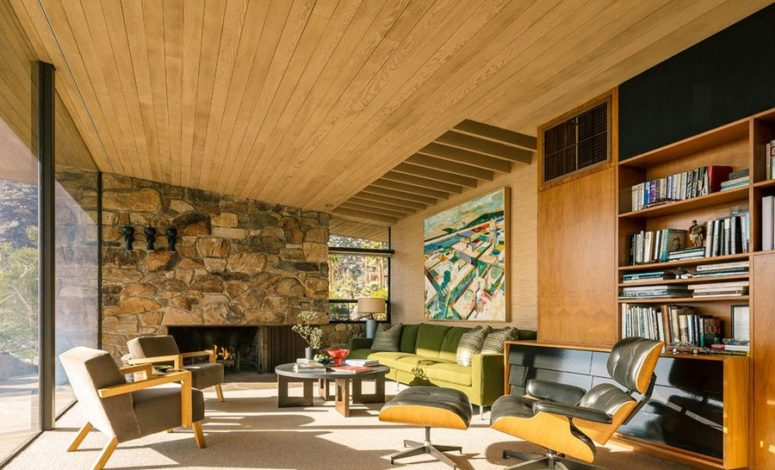 The living room features a natural wood ceiling with beams, s tone clad wall with a fireplace and a fine selection of comfy mid-century furniture