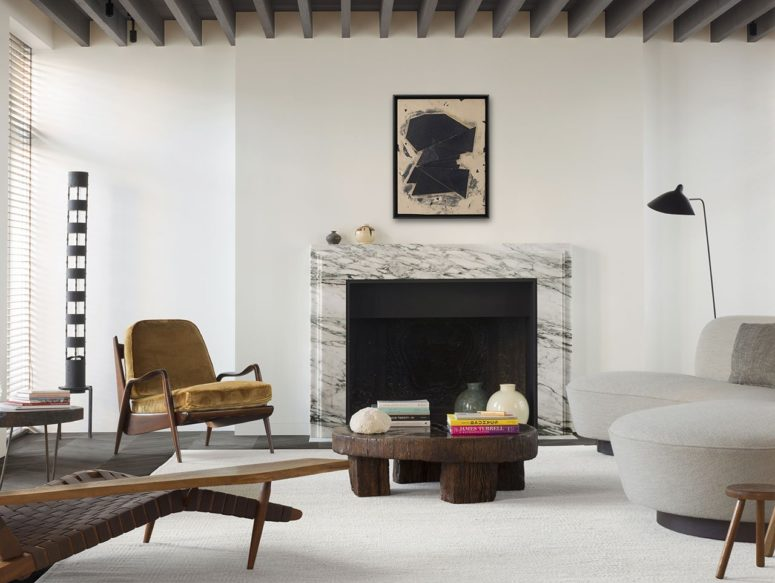 The living room features herringbone floors, wooden beams on the ceiling and a marble fireplace plus designer furniture