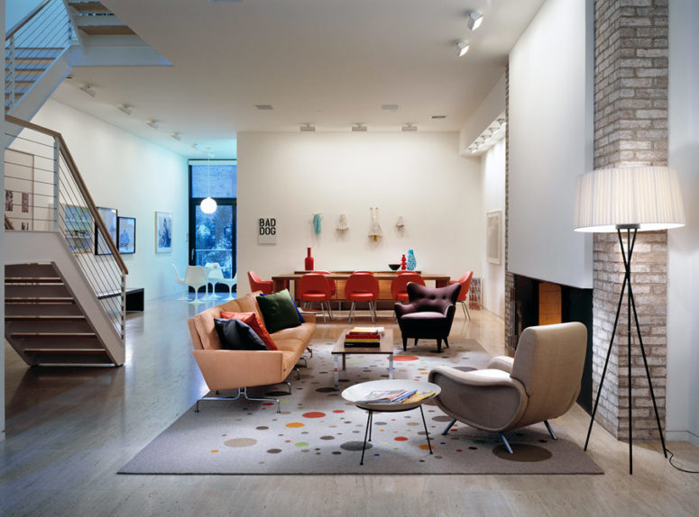 The living room is merged with a dining area, and you can see a cool fireplace with brick decor and designer furniture in hot red and orange