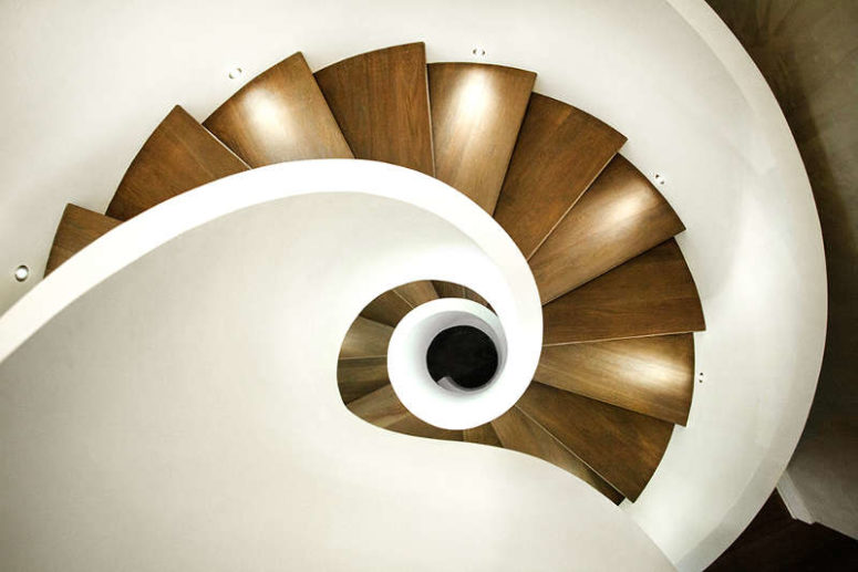 The staircase is done in modern white and with natural wood steps