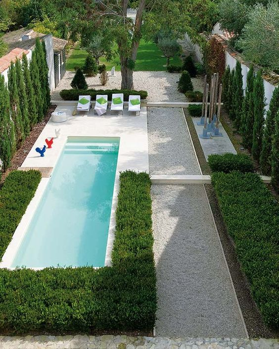 a gravel-covered backyard with perfect greenery and a small narrow pool