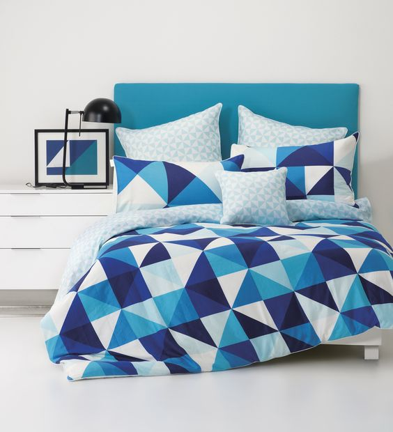 bold blue, navy and white triangle print bedding for a seaside space