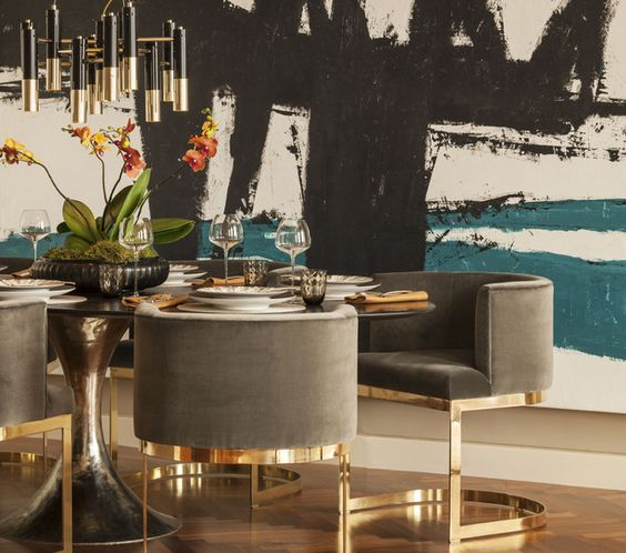gray barrel back dining chairs on gilded framing make the space chic and echo with the chandelier