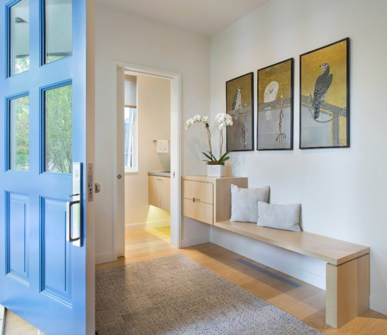 The entryway fetures artworks with light-colored wooden furniture, modern and chic