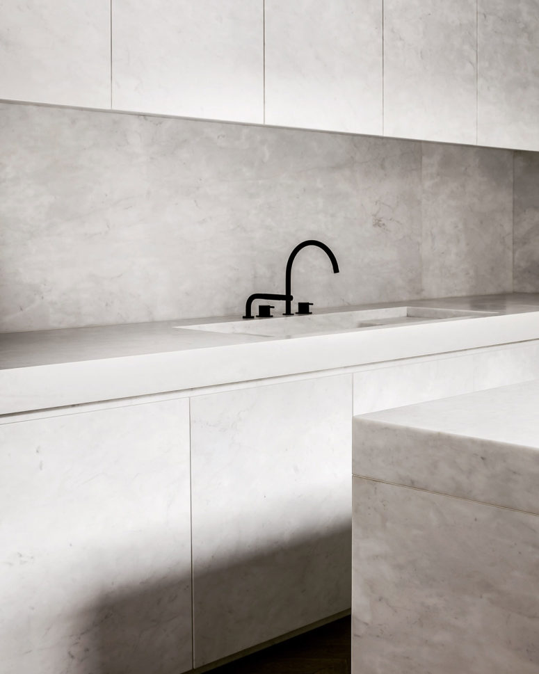 The kitchen is refined, fully clad with white marble and very chic, everything hidden and uncluttered