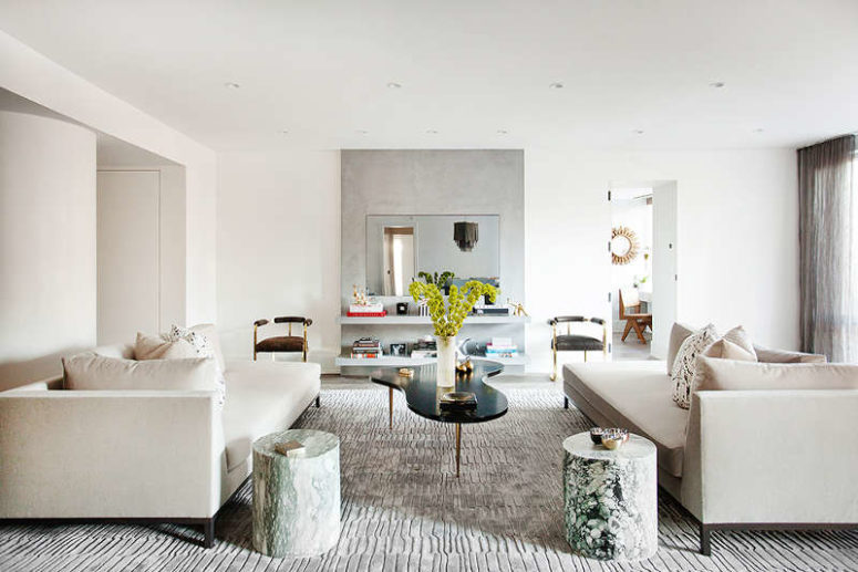 The living room is done in neutral shades liek creamy and grey, the furniture seems simple but the materials are refined