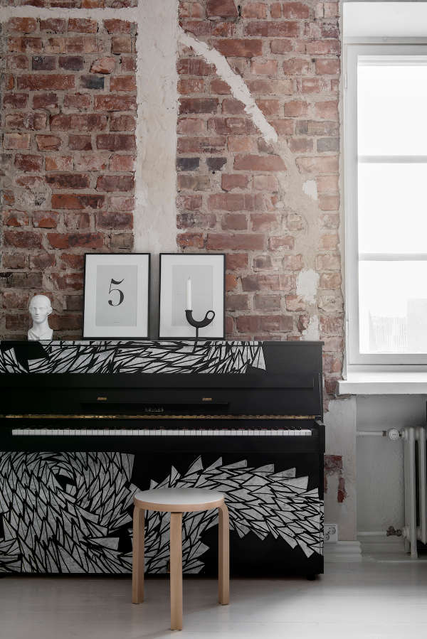 The piano in the living room is styled to minimalism with its black and painted white decor