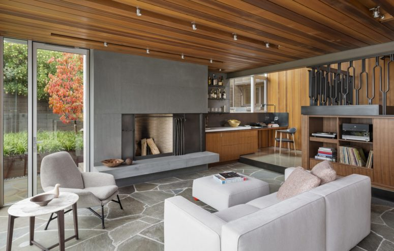 The walls are covered with different types of wood, the floor is done of stone and the fireplace is covered with concrete for a masculine feel
