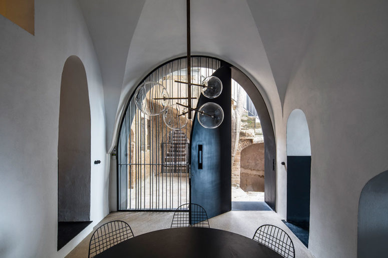This is an entrance with a black tin door, a black table and metal chairs and a cool modern glass bubble chandelier
