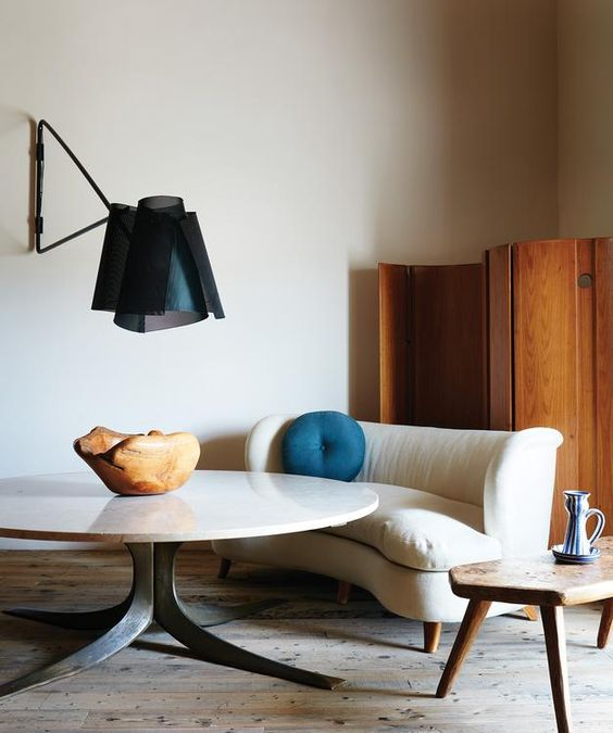 This space is very cozy and chic due to a statement wall lamp, a cute curved sofa and a wooden room divider