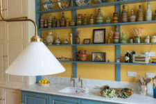 04 The kitchen countertop is clad with white marble, and the lamps are vintage brass ones