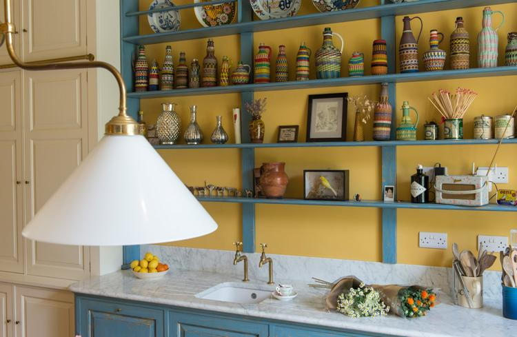 The kitchen countertop is clad with white marble, and the lamps are vintage brass ones