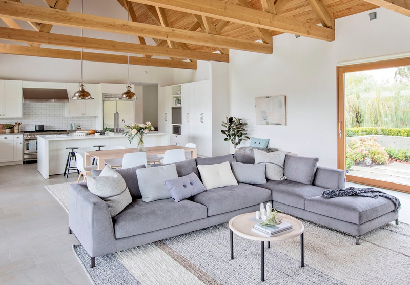 The living space features a large corner grey sofa, a comfy rug and those wooden beams on the ceiling add coziness