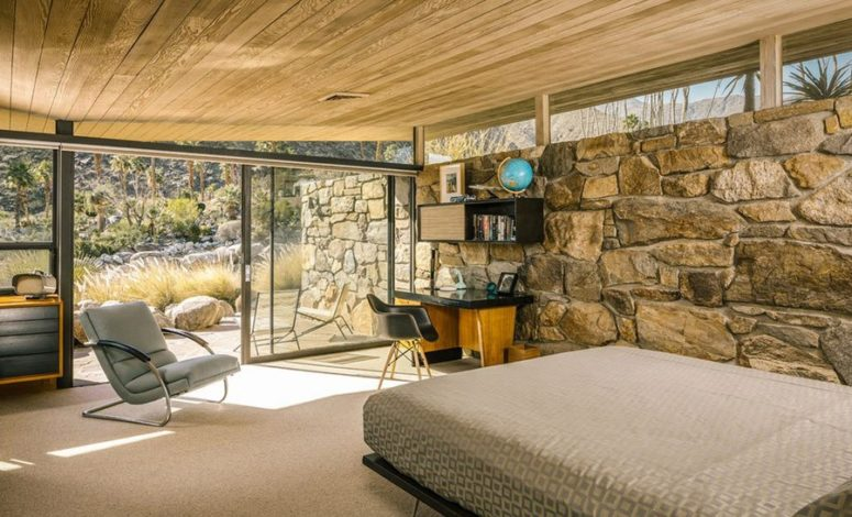 The master bedroom shows the same ceiling and a stone clad wall, comfy furniture in warm shades and an entrance to the terrace, this glazed wall lets enjoying the views