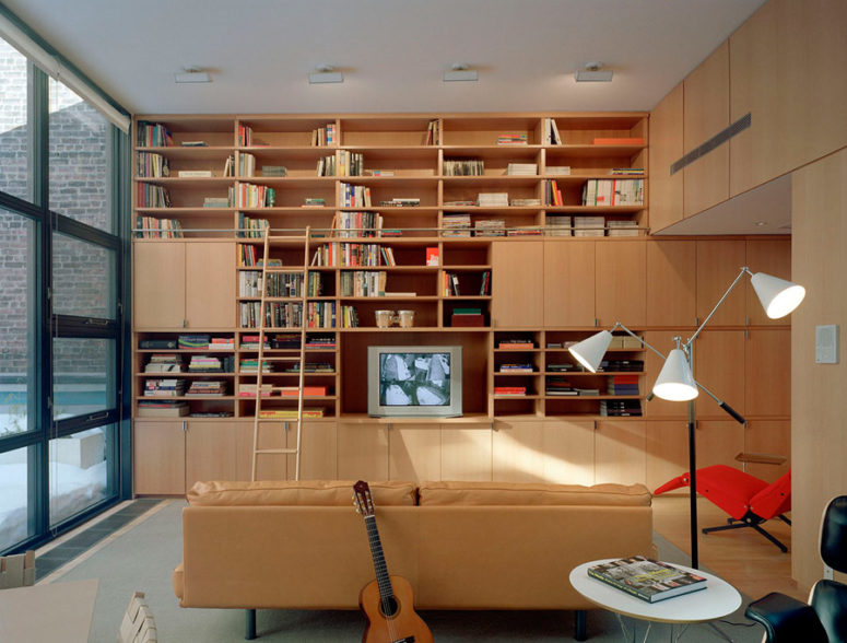 There's a library, fully decorated with light-colored wood, which makes it cozy and inviting, and there's a beige leather sofa