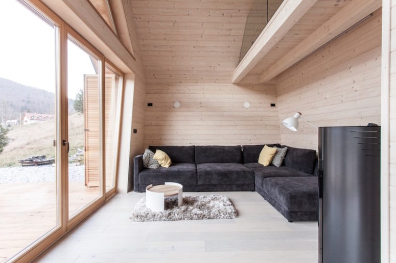 A glazed wall brings much natural light in and makes the interiors connected to the outdoor spaces