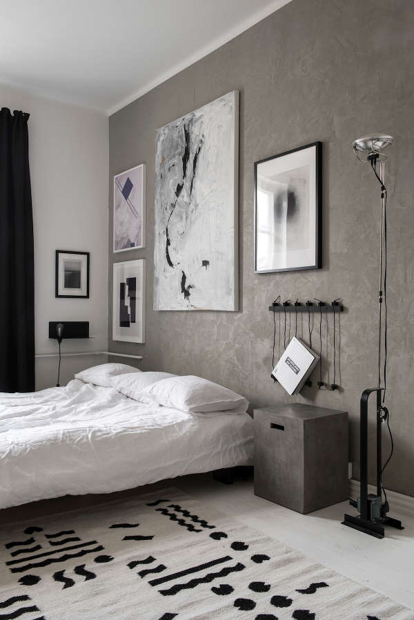 The bedroom has a grey accent wall and matching bedside tables, all the rest is laconic black and white