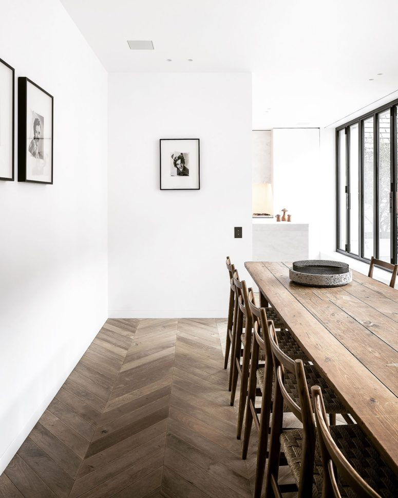 The dining space with a rustic wooden dining set is separated from the kitchen with a half wall