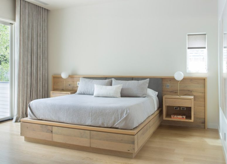 The master bedroom is modern and almost minimalist, with light-colored wooden platform bed and floating nightstands