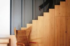05 The stairs is made of light-colored wood, there's a wicker chair and a restored wooden ceiling for coziness