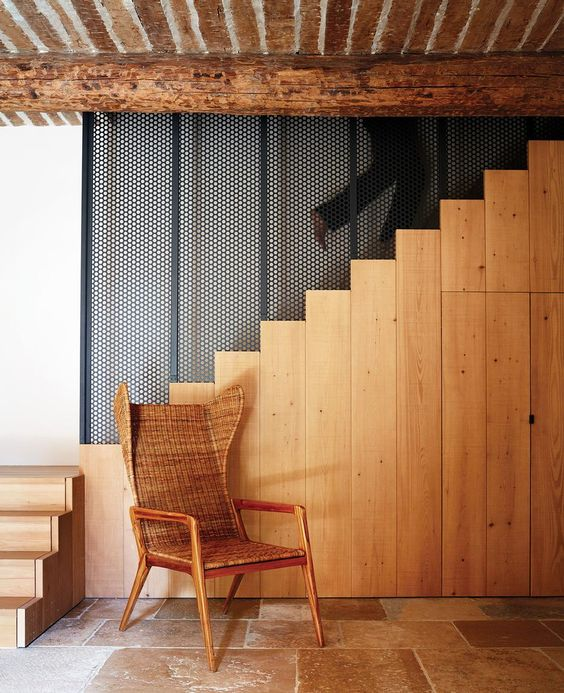The stairs is made of light-colored wood, there's a wicker chair and a restored wooden ceiling for coziness