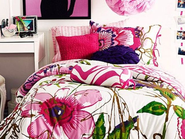 bold bedding in pink, green and purple with colorful pillowcases