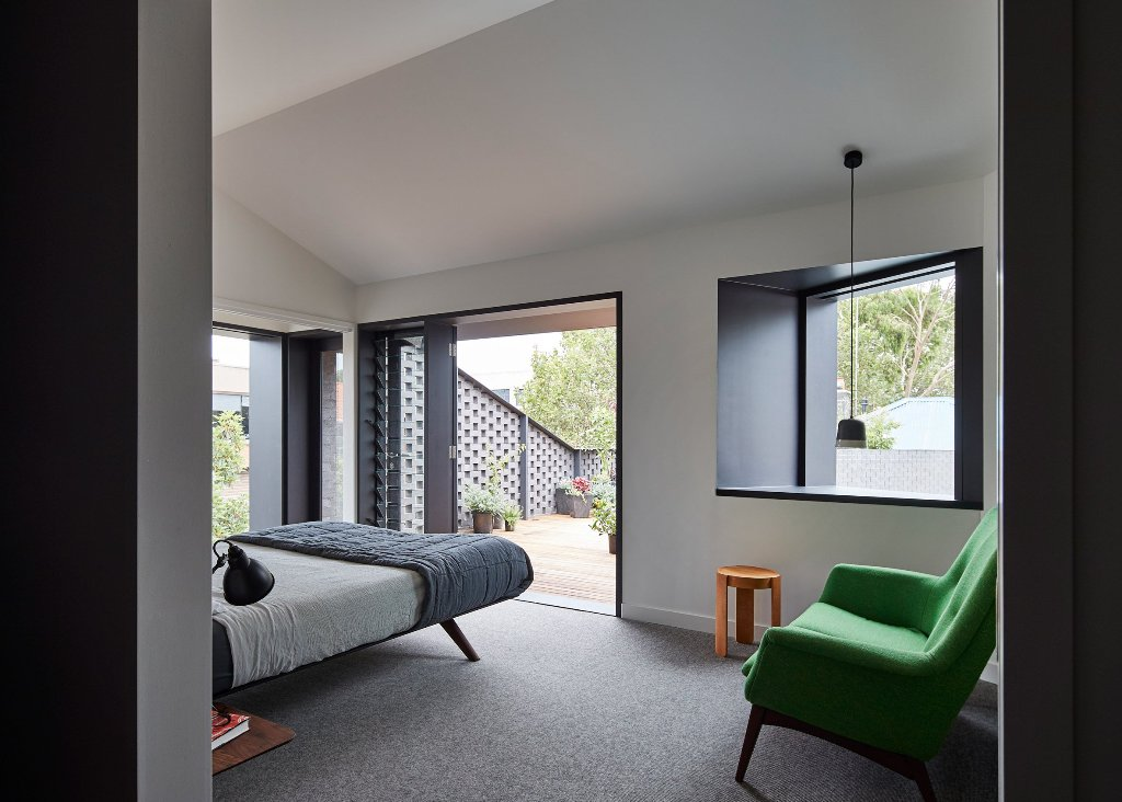 The bedroom is done in black and white, it's fully opened to outdoors with doors and windows and there's a bold green chair for a statement