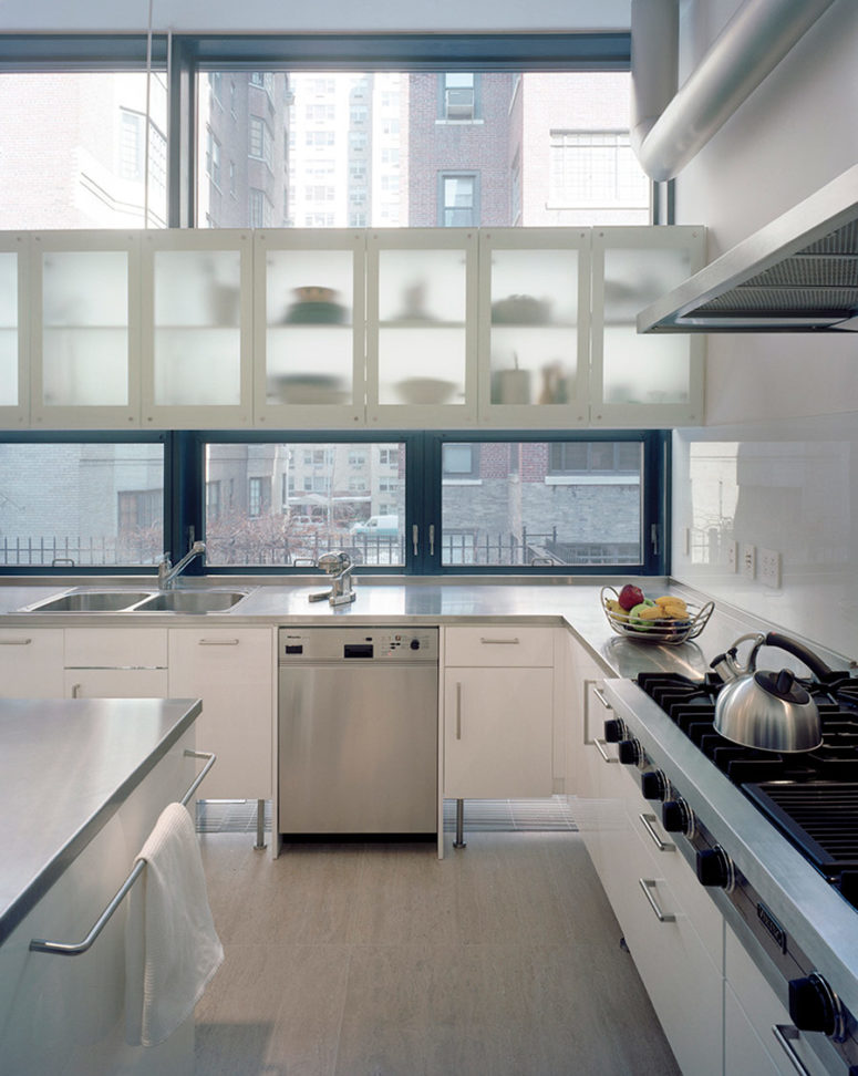 The kitchen is light-filled and spacious, with silver and white cabinets and steel surfaces