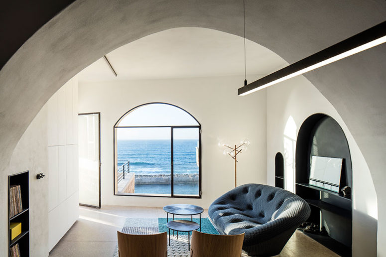 The living room is light-filled, with modern upholstered furniture and stunning sea views