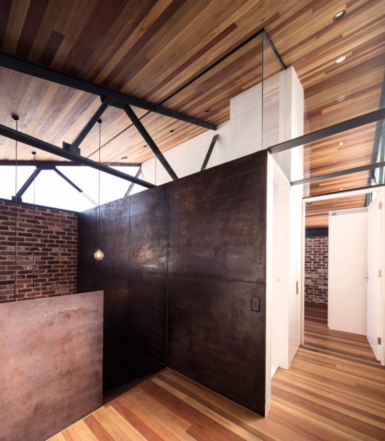 The shower has brick walls and rough metal dark ones, the industrial decor is perfectly shown here