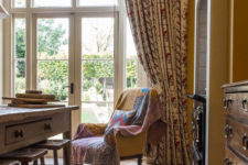 06 The space is made cozier with a wooden dresser, curtains and a vintage upholstered chair with carved legs