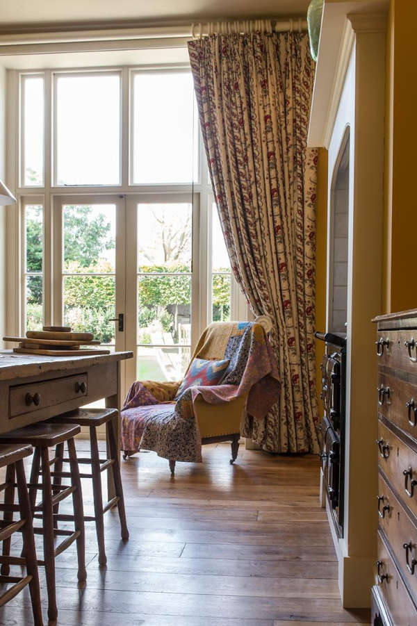 The space is made cozier with a wooden dresser, curtains and a vintage upholstered chair with carved legs