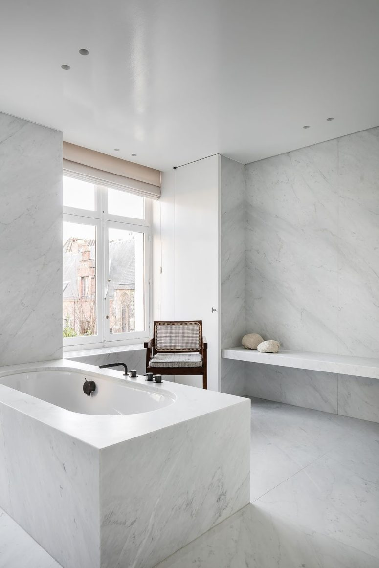 The bathroom is clad with white marble, it's filled with natural light through the window and there's much space