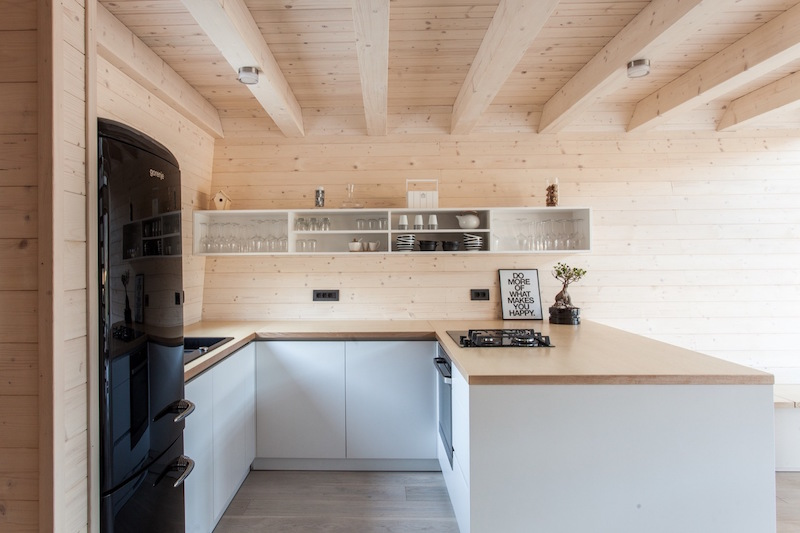 The kitchen corner is small and open, there's an U shaped counter and some built in appliances